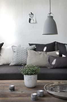 Grey sofa - layered with scatter cushions in greys - raw wood #livingroom