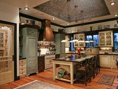 Stained and painted wood cabinetry and a copper range hood help create a welcoming and warm kitchen. What do you think about this recessed ceiling? Source: https://www.zillow.com/digs/Home-Stratosphere-boards/Luxury-Kitchens/