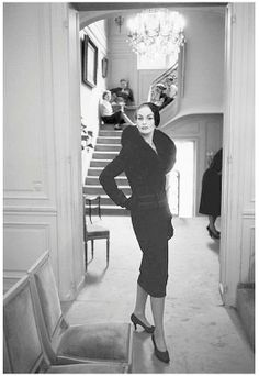 Model in an H-Line suit from Dior's Autumn/Winter collection of 1954, some of the seamstresses look on from the stairs, photo by Mark Shaw at Maison Dior, Paris, 1954