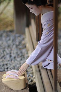 Maiko Toshichika reaching for her okobo (high wooden wedges)