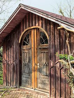 backyard shed - Victorian Arkansas wood and batten shed with detailed doors used as a he-cave/garage - Country Living via Atticmag