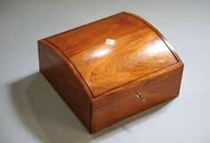 Beautiful handmade Jewelry Box. [The curved top is much in vogue these days and not all that difficult. Excellent how-to tells you what to do to make it. I might elevate the central divider in the lift-out box to make removing it easier; otherwise a good build]]