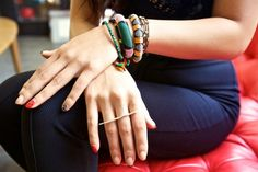 What a color-soaked combo! Linda Nguyen poses with her pretty adornments. The ring is by Bijules, and bracelets from her trips to Thailand and New York. (via refinery29)