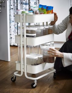 A woman grabbing a container from a kitchen utility cart