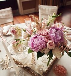 centerpieces are made with peonies, astilbe, ranunculus, spray roses, snapdragons, hydrangea, lisianthus, and garden roses, with foliage of lamb's ear, variegated pittosporum, and dusty miller.