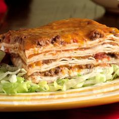 Ground beef, refried beans and tomatoes are combined with chiles and taco sauce, then  layered in a casserole with tortillas and cheese, and baked.
