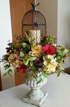 Ultra femanine Country French/Tuscan floral arrangement.  Rustic birdcage in a wreath of spring blooms sitting on an aged ceramic urn :).   Beautifully spring :)!!!