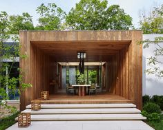 A wooden, tunnel-like structure bisects the main house allowing for a new entryway on one side and a covered dining room on the backside.