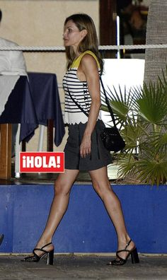 La reina Letizia se decantó por una minifalda en tono oscuro con cremallera frontal. La combina con un minibolso bandolera, sandalias de tacón ancho y el mismo top marinero que llevó horas antes en el posado en los jardines del Palacio de Marivent.