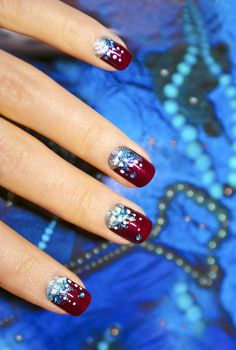 Holiday nails with a manicure with claret varnish and sparkles on the decorative background.