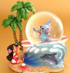 Photo courtesy of the DisneyStore UK website. Lilo & Stitch Description: Lilo and Stitch enjoy the sand and surf of Hawaii. Lilo Stitch, Lelo And Stitch, Cute Stitch, Disney Snowglobes, Disney Souvenirs, Stitch And Angel, Disney Love, Disney Disney, Disney Cars