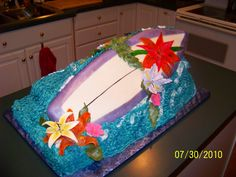 sweet 16 hawaii theme cake. the surf board if crispy treat covered in buttercream and marshmallow fondant. the flowers are gumpast and almond paste, the waves are the cake. there were 7 9x13 cakes stacked under the board. this cake was almost 75lbs when completed. all hand painted in edible food colors.