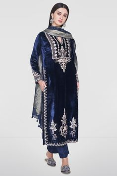 Crafted to perfection and intricately embroidered with our signature craft, Gota Patti, this navy velvet suit is perfect for any royal occasion. The Karuvaki Suit features a slit round neckline and full sleeves. Style Tip: All you need is a st Designer Kurtis, Indian Designer Suits, Velvet Suit Design, Velvet Dress Designs, Pakistani Formal Dresses, Pakistani Dress Design, Churidar, Anarkali, Lehenga