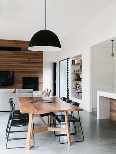 Contemporary dining room with wooden table, minimalist black dining chairs…