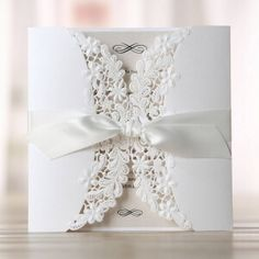 Elegant invitation with intricate floral laser cut design, wrapped in white satin ribbon. Printed in raised ink on a smooth pearl paper and customisable inner card colour.