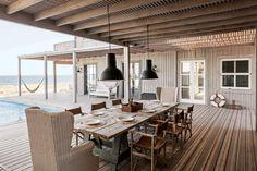 La larga mesa con caballetes se hizo con tablones de la obra. Tiene sillones de ratán en las cabeceras y sillas de director de loneta color camel ($5.100 c/u). Iluminan dos grandes lámparas industriales ($4.200, Paul French Gallery y Paul Beach House). / Gentileza Sofía Oneto