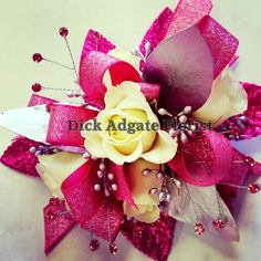 White Sweetheart Roses, silver seeded eucalyptus, hot pink ribbon, leaves and spray gems. Homecoming and Prom corsages. Dick Adgate Florist original