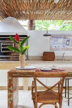 Varanda com churrasqueira tem bancada de granito e mesa comprida de madeira.