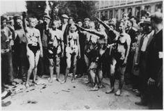 Femmes belges qui avaient collaboré avec les Allemands sont rasés, goudron et de plumes et forcé de donner un salut nazi.