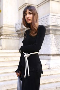 The simple white knotted belt on this black dress is the focal point of the outfit.