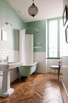Gorgeous bathroom with painted claw foot tub and herringbone wood floors