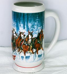 "CS678 - 2007 "" Winter's Calm "" Holiday stein. This 7"" Holiday stein was made in Brazil by Ceramarte. Artist Jeff Wack features the Clydesdales Hitch laden with evergreens in a snowy woodland scene."