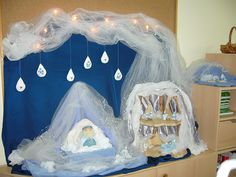 Winter nature table with winter gnome house and winter king on his throne. Above you can see ice drops with little ice gnomes.