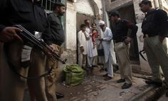 Police stand guard as a polio worker waits to give polio vaccine drops to children at a street in Peshawar, the capital of Khyber-Pakhtunkhwa province March 30, 2014. REUTERS/Fayaz Aziz