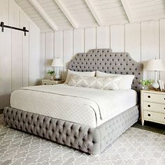 A linen-upholstered king-size bed was designed with intricate tufting that extending from the headboard to the rails.