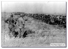 Two German soldiers look on curiously as captured Soviet soldiers file past. Stalingrad. September, 1942.