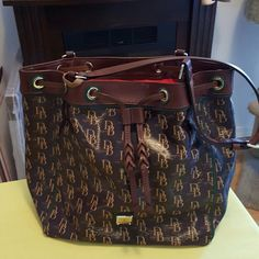 Dooney and Bourke Sutton Bucket Bag Drawstring large bucket bag, 81% PVC/19% cotton, trim 100% leather, lining 100% red cotton.  Four bottom feet, front wall slip pocket, metal logo plate very clean no scratches, adjustable shoulder straps. Dooney & Bourke Bags Shoulder Bags