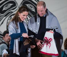 Draped in traditional First Nation blankets, William and Kate hold vests they were given for Prince George and Princess Charlotte during the ceremony in Bella Bella