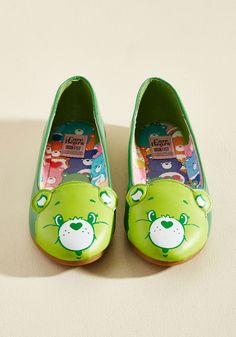 Face Your Cheers Vegan Flat | Mod Retro Vintage Flats | ModCloth.com  Proclaim your proclivity for positivity by sporting these Care Bear ballet flats from Iron Fist! Bright green in hue with the iconic visage of Good Luck Bear atop the toes, this vegan faux-leather pair - an exclusive to ModCloth - helps you take on the day with stunning optimism.
