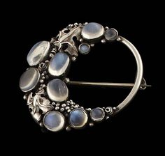 Dorrie Nossiter (attrib.). An Arts and Crafts brooch, open circular form, applied with a crescent collet set with graduated oval and circular cut moonstone cabochons with clusters of beads and foliate scrolls between 4cm diameter. Sold by Lyon and Turnbull, 7 November 2012.