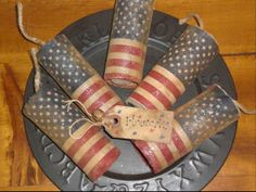 """use an American flag material secured around paper cylinders. Next, a jute string has been inserted in the middle of each firecracker and polyester fiberfill has been stuffed inside of each cylinder. These firecrackers measure approximately 4"""" tall and 1 ¾""""  wide.  Grunge w/ a solution of coffee, vanilla and cinnamon.  Sprinkle mika flakes over."""