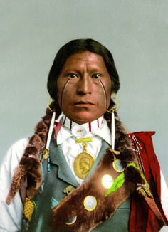 An Apache chief, James A. Garfield. An early color photograph, produced using a Swiss photolithographic technique known as the Photochrom process.