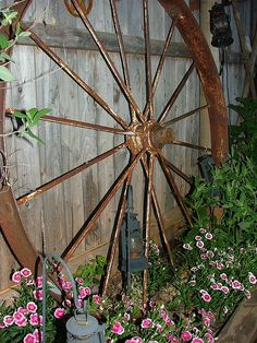Wagon wheel against a fence with flowers in the foreground