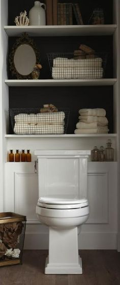 Great use of space. Small bathnroom design with built-in shelves with backs of shelves painted black, wire baskets, ivory bath towels, wire & wood wastebasket and vintage bottles.