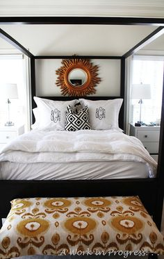large sunburst mirror, ikat +david hicks, white bedding,  monogrammed shams
