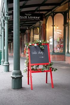 Creative use of a child's chalkboard easel as signage (painting it red and adding silk flowers are a great idea).