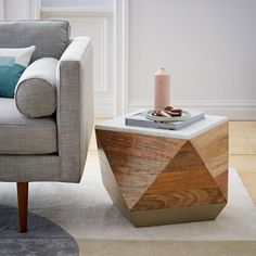 Creative firm Roar + Rabbit designs textiles, furniture and home accessories that blend modern style with whimsical details. We worked with them to create this sculptural, geometric side table. Made from solid mango wood and partially wrapped in hand-hammered metal, it's finished with a solid marble top for a colourblocked effect.