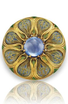 LOUIS COMFORT TIFFANY, TIFFANY & CO. - A SAPPHIRE, ENAMEL AND GOLD PENDANT-BROOCH, CIRCA 1910. The circular plaque centring upon a circular cabochon sapphire, within a blue and green plique-à-jour enamel and gold filigree floral surround, 1 1/2 ins., with French import mark for 18k gold, with collapsible pendant hoop. Signed Tiffany & Co. #LouisComfortTiffany
