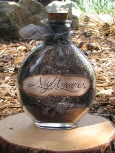"""What do you do about a terrible nightmare that keeps coming back? You store it in your magical Nightmares Bottle! This vintage look bottle is filled with mystical black """"dust"""" that only the dark night can bring as well as tiny antiqued papers with classic nightmare themes on them that you may want to keep bottled up! Outside bottle has shimmery black tulle wrapped around the neck. Bottle cork has a crescent moon seal on the top in midnight black and comes sealed in black candle wax but can…"""