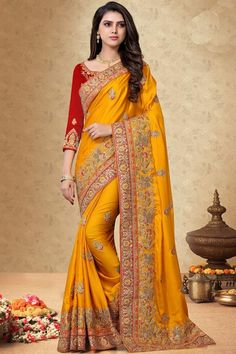 Turmeric Yellow silk saree with red silk blouse, embellished with dori work, resham work and sequins work. Saree with Round Neck, Quarter Sleeve. It comes with unstitch blouse, it can be stitched 32 to 58 sizes. # turmeric yellow#silk # wedding wear #saree #blouse #Andaazfashion #UK