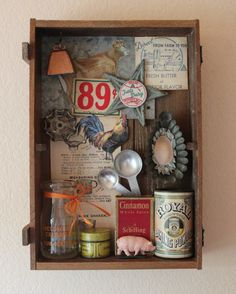 This a found object assemblage of vintage farmhouse items. The assemblage is in 14X 9.5 rustic wooden box ready to hang with a wooden bracket. The box is a vintage wine box. The items within the box are vintage farmhouse and kitchen items: a vintage cream bottle, an old tin, an old spice box, vintage measuring spoons, a vintage baking soda tin, a vintage baking mold an old iron star, a small plastic farm animal pig , a small metal faucet handle, and a small cow bell. The paper items included…