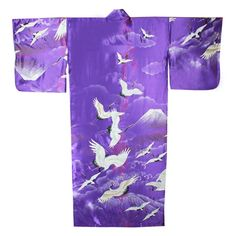 This Kimono is adorned with cranes flying in the sky above Mt Fuji with sprinkles of pink cherry blossoms on a beautiful purple polyester background. Made in Japan, this traditional Japanese Kimono has butterfly styled sleeves and a matching belt.