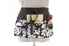 An apron that is functional and stylish, what a great combination! Free your hands and have everything where you need it, round your waist. This apron features 6 useful pockets made from a simply stylish black and white scroll cotton fabric - a central zip pocket with a pouch pocket