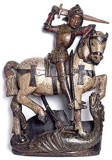 Medieval wood carving of a knight in armour on horseback, raising his sword to strike at a dragon. About 11th cent. Herbert Museum and Gallery