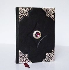 Handcrafted, black The glass stone in front of diary decorate the art book and is perfect for wizard, witches and magic spells. This black diary is made from genuine leather. Handmade Notebook, Notebook Ideas, Leather Photo Albums, Creation Art, Magic Spells, Small Shops, Purple Glass, Leather Journal, Bookbinding