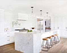 All white kitchen with marble island and wood stools